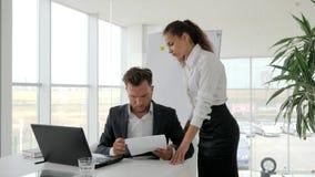 L'assistant maintiennent dans le rapport de travail de bras, document de signe de patron à la table, documentation disponible de  banque de vidéos