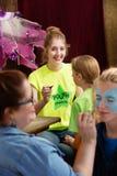 L'assistant temporaire de camp aide l'acteur d'enfant image libre de droits