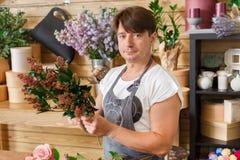 L'assistente del fiorista dell'uomo nella consegna del negozio di fiore fa il mazzo Fotografie Stock Libere da Diritti