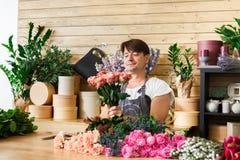 L'assistente del fiorista dell'uomo nella consegna del negozio di fiore fa il mazzo rosa Immagini Stock