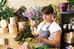 L'assistente del fiorista dell'uomo nella consegna del negozio di fiore fa il mazzo rosa Fotografie Stock