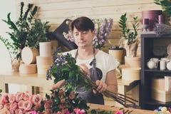 L'assistente dell'uomo nella consegna del negozio di fiore fa i mazzi Fotografia Stock