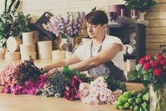 L'assistente dell'uomo nella consegna del negozio di fiore fa i mazzi Fotografie Stock