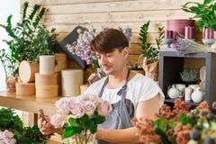 L'assistente dell'uomo nella consegna del negozio di fiore fa il mazzo rosa Fotografie Stock