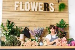 L'assistente dell'uomo nella consegna del negozio di fiore fa il mazzo rosa Immagini Stock