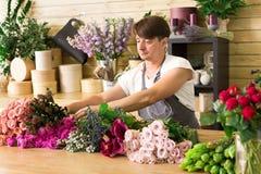 L'assistente dell'uomo nella consegna del negozio di fiore fa il mazzo rosa Immagini Stock Libere da Diritti
