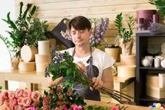 L'assistente dell'uomo nella consegna del negozio di fiore fa il mazzo rosa Immagine Stock Libera da Diritti