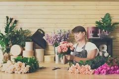 L'assistente dell'uomo nella consegna del negozio di fiore fa il mazzo rosa Fotografia Stock Libera da Diritti