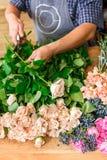 L'assistente dell'uomo nella consegna del negozio di fiore fa il primo piano rosa del mazzo Fotografia Stock