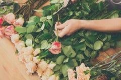 L'assistente dell'uomo nella consegna del negozio di fiore fa il primo piano rosa del mazzo Immagine Stock Libera da Diritti