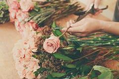 L'assistente dell'uomo nella consegna del negozio di fiore fa il primo piano rosa del mazzo Fotografia Stock Libera da Diritti