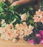 L'assistente dell'uomo nella consegna del negozio di fiore fa il primo piano rosa del mazzo Immagine Stock
