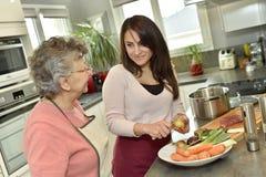 L'assistente di Homecare contribuisce a cucinare per una donna anziana fotografia stock