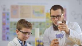L'assistente di laboratorio con l'allievo esamina cocente a vapore i liquidi variopinti in boccette video d archivio