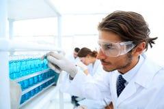 L'assistente di laboratorio negli occhiali di protezione e un laboratorio ricoprono di provetta Immagini Stock