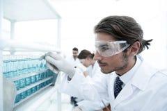 L'assistente di laboratorio negli occhiali di protezione e un laboratorio ricoprono di provetta Fotografie Stock Libere da Diritti