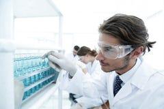 L'assistente di laboratorio negli occhiali di protezione e un laboratorio ricoprono di provetta Fotografia Stock Libera da Diritti
