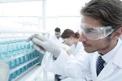 L'assistente di laboratorio negli occhiali di protezione e un laboratorio ricoprono di provetta Immagini Stock Libere da Diritti