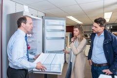 L'assistente dimostra il frigorifero alle giovani coppie fotografia stock