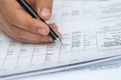 L'assistente tecnico controlla i calcoli. Immagine Stock Libera da Diritti
