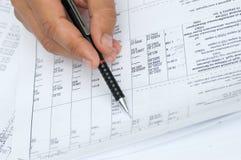L'assistente tecnico controlla i calcoli. Fotografie Stock