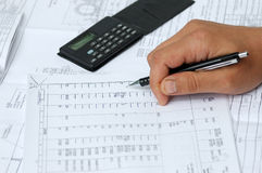 L'assistente tecnico controlla i calcoli. Fotografie Stock Libere da Diritti