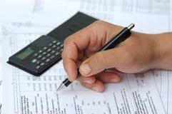 L'assistente tecnico controlla i calcoli. Fotografia Stock