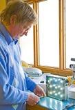 L'assistente tecnico elettronico verifica una sorgente luminosa. Immagine Stock Libera da Diritti