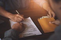 L'associé donnent l'argent de paiement illicite dans l'enveloppe à un autre homme d'affaires et le pointage au contrat d'autorisa photographie stock libre de droits