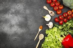 L'assortiment des légumes frais poivrent, des tomates-cerises, des oignons, ail, brocoli, laitue sur un fond foncé et diverse épi Image libre de droits