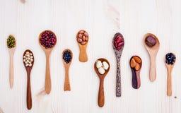 L'assortimento dei fagioli e delle lenticchie in cucchiaio di legno ha installato su di legno immagini stock libere da diritti