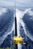L'asta e la bobina del gran gioco di pesca sulla barca svegliano Immagini Stock Libere da Diritti