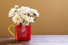 L'aster blanc fleurit dans la tasse de café rouge avec de GRANDES lettres d'AMOUR sur la table en bois Photographie stock