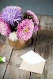 L'aster multicolore fleurit le bouquet, la carte de voeux blanche de blanc et l'enveloppe de papier de métier sur la table en boi Photo stock