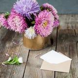 L'aster multicolore fleurit le bouquet, la carte de voeux blanche de blanc et l'enveloppe de papier de métier sur la table en boi Photos stock