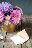 L'aster multicolore fleurit le bouquet, la carte de voeux blanche de blanc et l'enveloppe de papier de métier sur la table en boi Photos libres de droits
