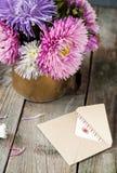 L'aster multicolore fleurit le bouquet, la carte de voeux blanche de blanc et l'enveloppe de papier de métier sur la table en boi Image libre de droits