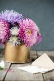 L'aster multicolore fleurit le bouquet, la carte de voeux blanche de blanc et l'enveloppe de papier de métier sur la table en boi Images libres de droits