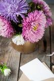 L'aster multicolore fleurit le bouquet, la carte de voeux blanche de blanc et l'enveloppe de papier de métier sur la table en boi Photographie stock libre de droits