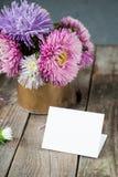 L'aster multicolore fleurit le bouquet, la carte de voeux blanche de blanc sur la table en bois rustique et le fond gris-foncé Mo Photos libres de droits