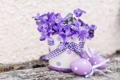 L'aster pourpre eggs sur les points et le vase avec les violettes pourpres Images libres de droits