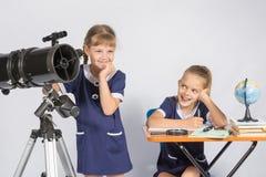 L'astronome de fille mystérieusement examine la distance, un camarade de classe avec un sourire regardé lui images stock