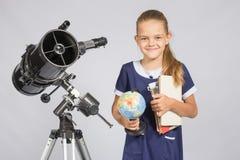 L'astronomo della ragazza è un telescopio con un globo ed i libri nelle mani Fotografie Stock