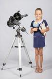 L'astronomo della scolara è un telescopio con un globo ed i libri nelle mani Fotografia Stock