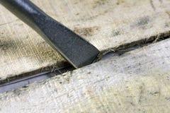 L'astuce de l'outil pour retirer des clous ou un tournevis large est insérée dans l'espace vide entre les conseils en bois Le con photo stock