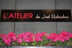 L'atelier de Joel Robuchon Sign och blommor arkivbilder