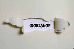 L'atelier de mot apparaissant derrière le papier déchiré Photographie stock libre de droits