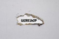 L'atelier de mot apparaissant derrière le papier déchiré Images stock
