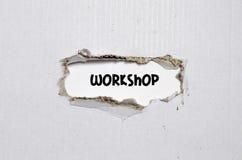 L'atelier de mot apparaissant derrière le papier déchiré Photographie stock