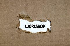 L'atelier de mot apparaissant derrière le papier déchiré Photos stock